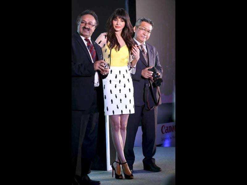 Bollywood actor Anushka Sharma (C), President and CEO Canon India Kazutada Kobayashi (R) and Executive Vice President of Canon India Alok Bharadwaj display cameras during the launch of a new range of Canon cameras, including Wi-Fi enabled ones in New Delhi. (AP Photo)