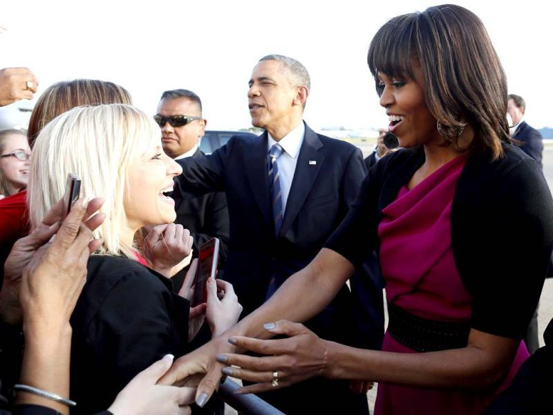 President Barack Obama and first lady Michelle Obama greet well wishers after they step off Air Force One at Dallas Love Field as they arrive to attend the George W Bush presidential library dedication and the memorial for victims of the fertilizer plant explosion in West, Texas. (AP Photo)