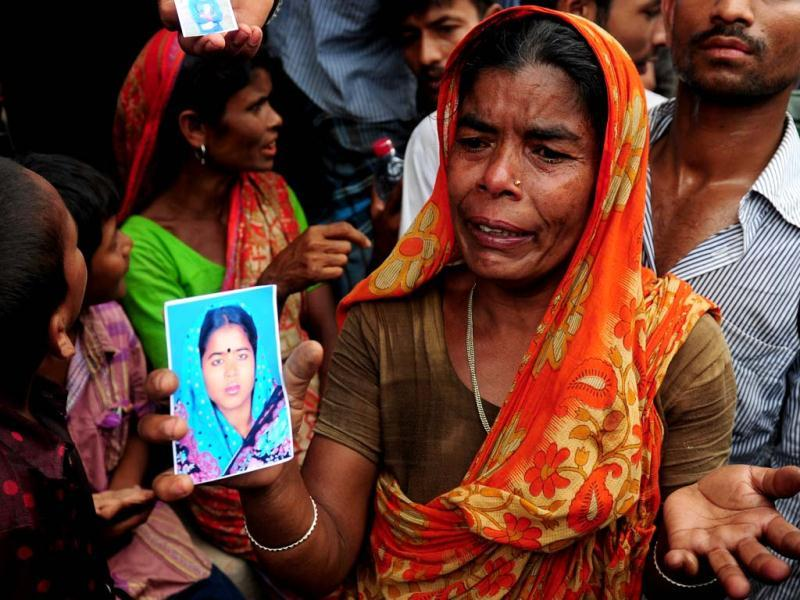 A Bangladeshi woman shows a portrait of her missing daughter in-law, believed trapped in the rubble following the collapse of the Rana Plaza building in Savar, on the outskirts of Dhaka. AFP Photo/Munir uz Zaman