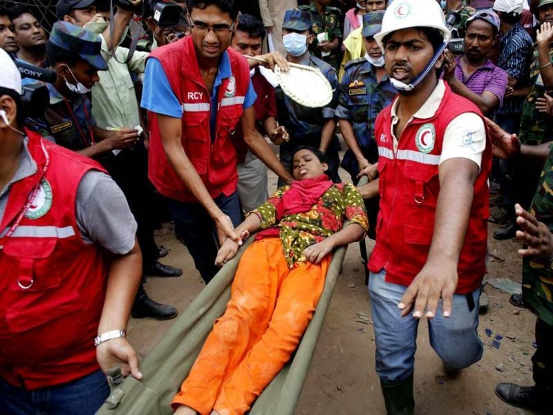 Rescue workers carry a survivor, who was trapped inside the rubble of the collapsed Rana Plaza building, in Savar, 30 km (19 miles) outside Dhaka, Bangladesh. Reuters
