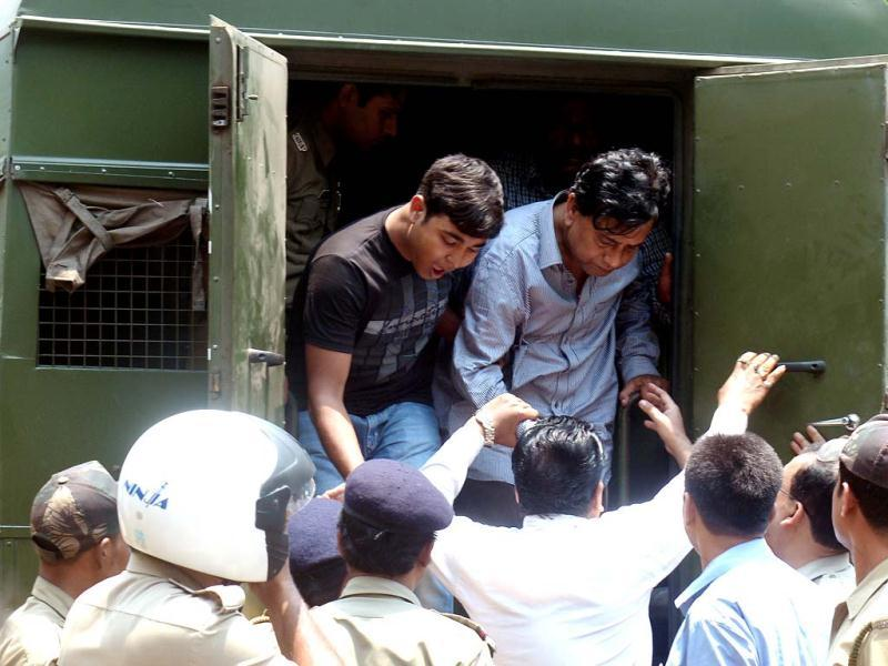 Police escort arrested chairman of Saradha group, Sudipta Sen (R top), from a police van to the court in Kolkata. AFP photo