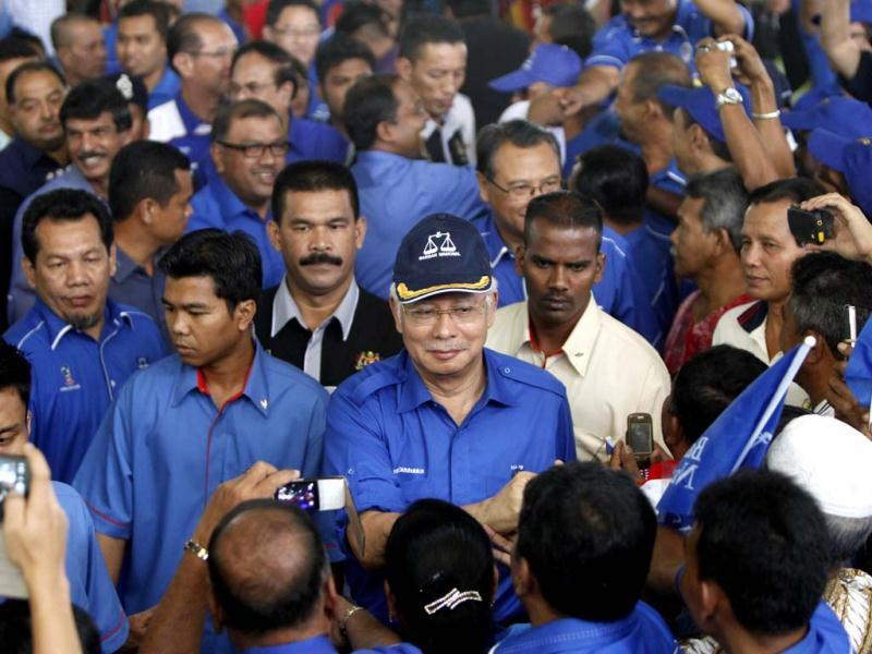 Malaysian Prime Minister Najib Razak, center, is welcomed by supporters as he arrives for an election campaign rally in Kuala Kangsar, Perak state, Malaysia. Malaysian will head to the polls to cast their votes in general elections on May 5. (AP Photo/Lai Seng Sin)