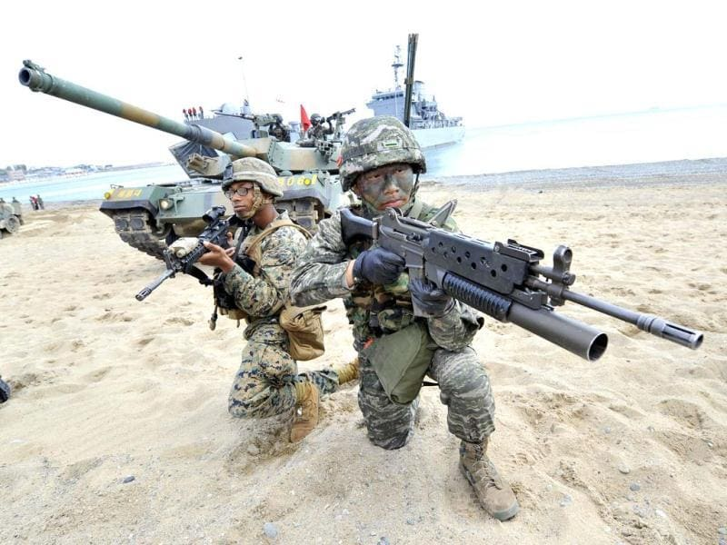 South Korean (R) and US (L) Marines take a position on the seashore during a joint landing operation by US and South Korean Marines in Pohang, 270 kms southeast of Seoul. The US and South Korea staged a military landing exercise as the Korean peninsula was already engulfed in a cycle of escalating tensions triggered by the North Korea's nuclear test in February. AFP PHOTO