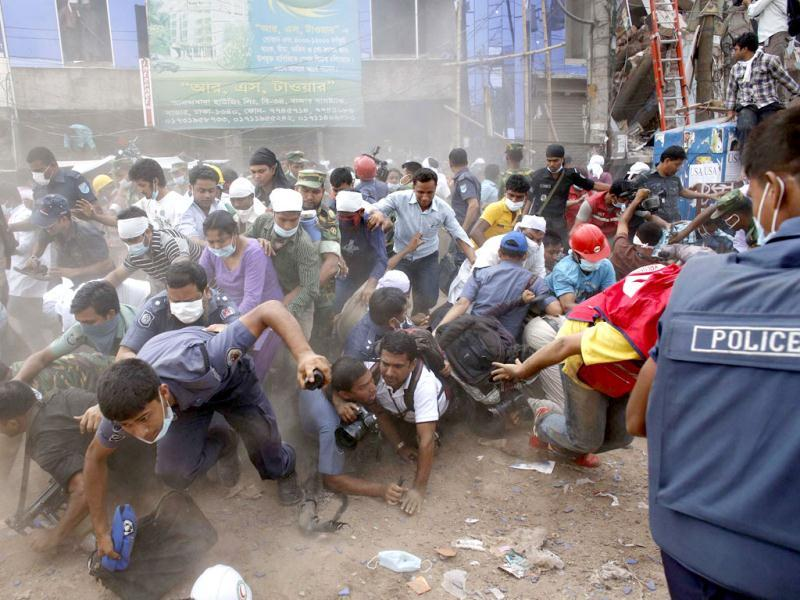 Rescue workers, army personnel, police and members of media run after they heard someone shouting that a building next to Rana Plaza is collapsing during a rescue operation in Savar, 30 km (19 miles) outside Dhaka. Reuters