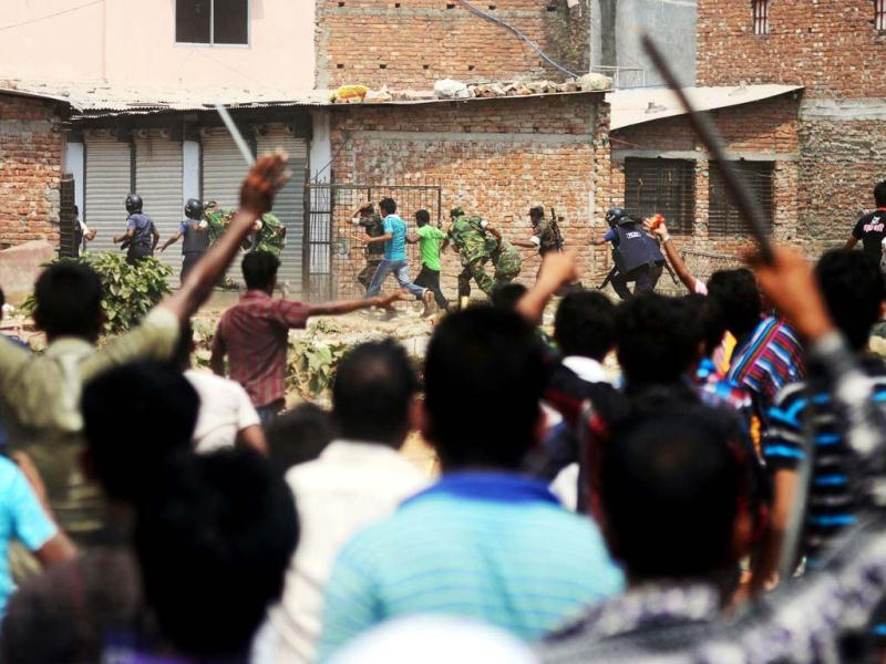 Bangladeshi Army personal and police run as villagers chase them, after relatives burst into angry protests, at the disaster site of an eight-storey building collapsed 48 hours earlier in Savar, on the outskirts of Dhaka. AFP PHOTO