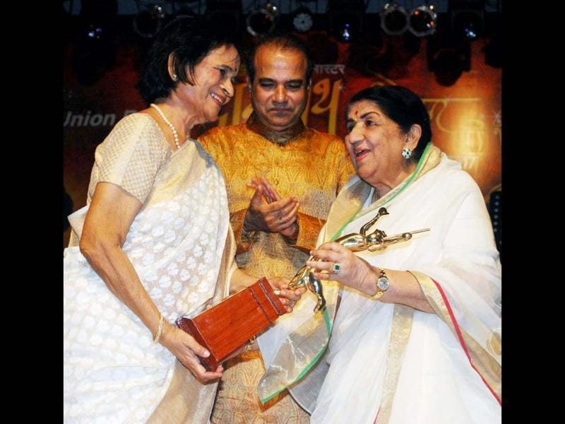 Legendary singer Lata Mangeshkar presenting award to eminent writer Neeta Tai at the gala. (UNI Photo)