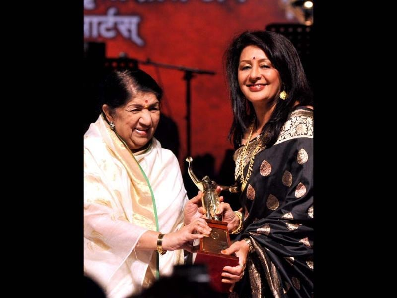Lata Mangeshkar presents an award to Marathi actress Vandana Gupte during Master Dinanath Mangeshkar Award Ceremony. (AFP Photo)