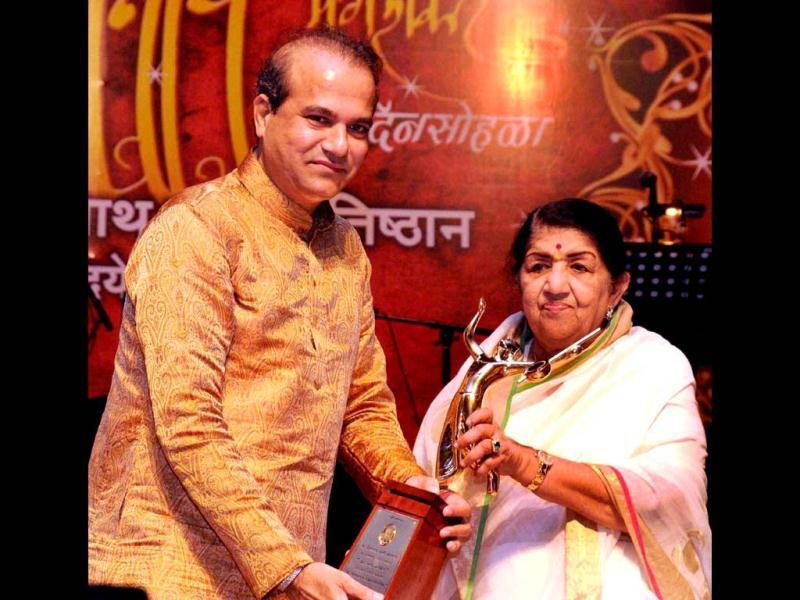 Lata Mangeshkar honouring Suresh Wadkar, for his contribution in the singing industry, during her father Master Dinanath Mangeshkar's Anniversary in Mumbai. (PTI Photo)