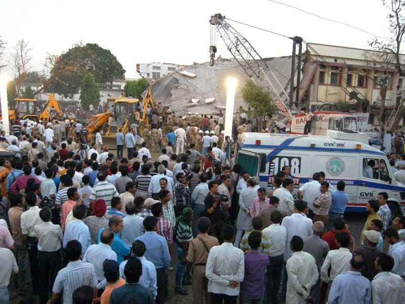 People look on during a rescue operation after a portion of the two-storied Kasturba Gandhi Hospital collapsed in Bhopal. (PTI)