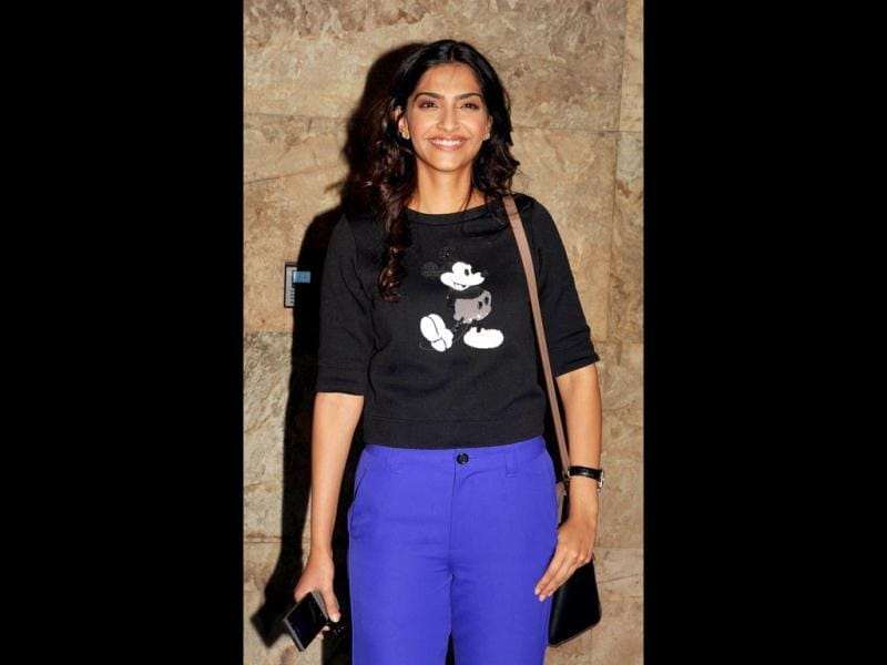 Sonam Kapoor is all smiles in a Mickey Mouse tee and indigo coloured pants. (AFP Photo)