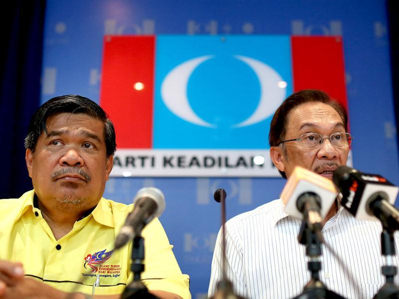 Malaysia's opposition leader Anwar Ibrahim (R) speaks as Mohamad Sabu, deputy president of the opposition Pan-Malaysian Islamic Party (L), looks on during a press conference at their party headquarters ahead of the country's 13th general elections in Kuala Lumpur. (AFP)