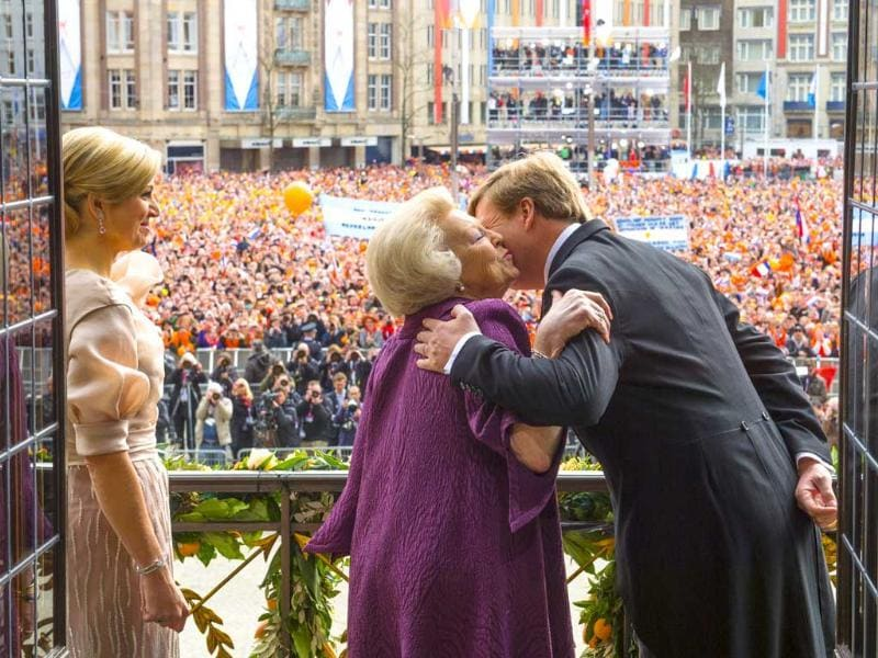 In this handout photo Dutch King Willem-Alexander kisses his mother Dutch Princess Beatrix as Dutch Queen Maxima looks at the well wishers in the crowd after the signing of the Act of Abdication at the Royal Palace in Amsterdam, The Netherlands. AP