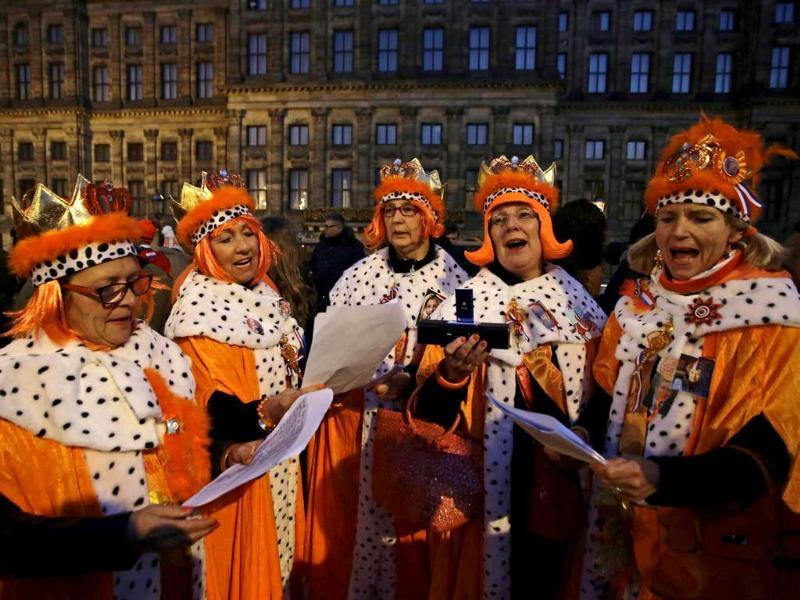 People wait outside the Royal Palace in Amsterdam. The Netherlands is preparing for Queen's Day which will also mark the abdication of Queen Beatrix and the investiture of her eldest son Willem-Alexander. Reuters