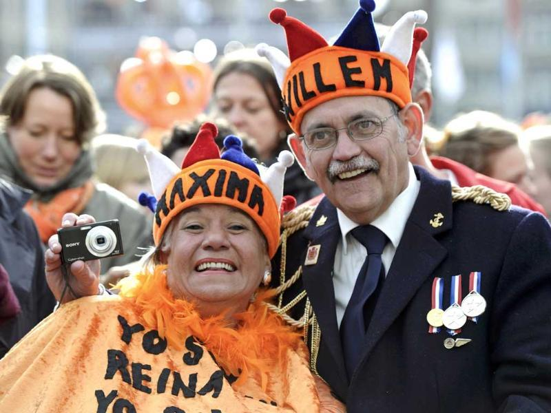 A couple waits for Queen Beatrix's abdication ceremony outside the Royal Palace in Amsterdam. Reuters