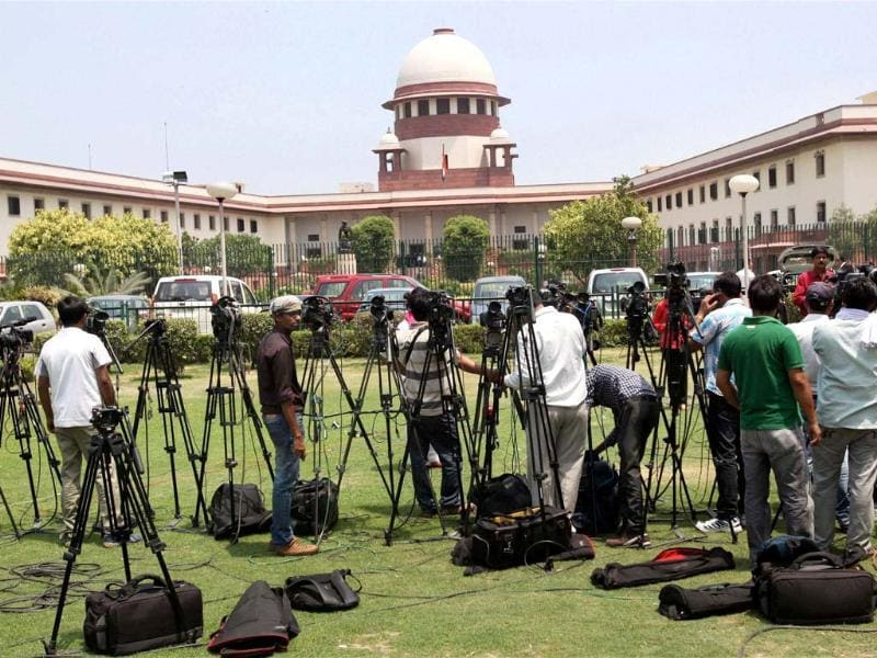 Media personnel fix their cameras in the lawn of Supreme Court during a hearing on the coal blocks allocation case in New Delhi. PTI/Atul Yadav
