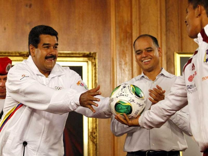 Venezuela's President Nicolas Maduro reaches for a ball from a member of the Venezuela's Under-17 soccer team, during a news conference in Caracas. Reuters