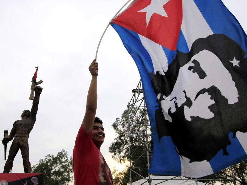 A supporter of the ruling Sandinista party holds up a Cuban national flag with the image of revolutionary leader Ernesto 'Che' Guevara during early May Day celebrations in Managua. Reuters