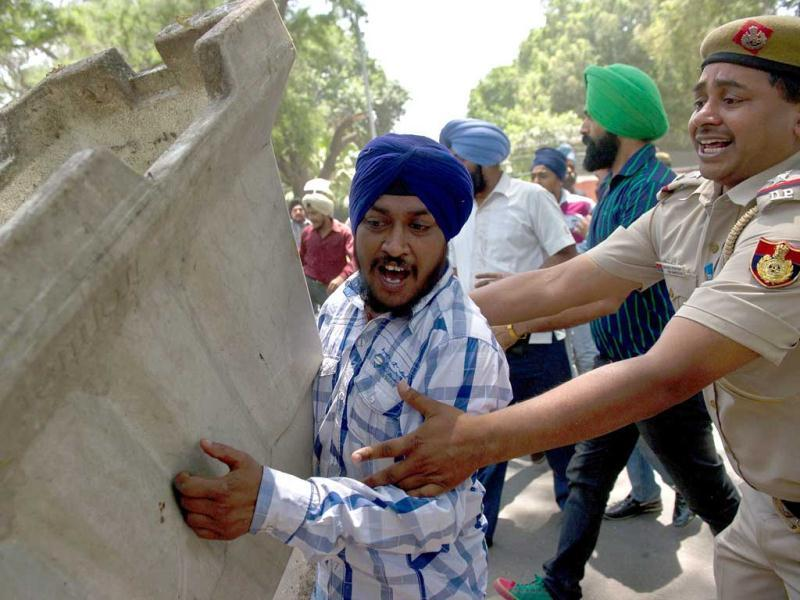 Policeman attempts to restrain a Sikh protestor as he overturns a road block outside Congress Party president Sonia Gandhi's residence in New Delhi. (AFP)