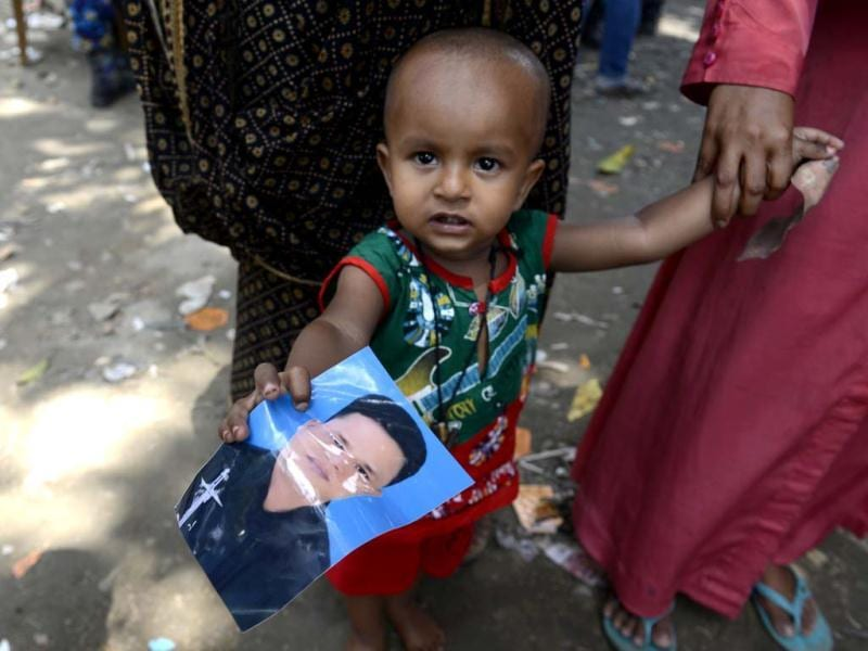 A young child holds a picture of his father who was missing since the collapse of the garment factory building in Savar, near Dhaka. Rescuers found more bodies in the concrete debris of the collapsed garment factory building Thursday and authorities said it may take another five days to clear the rubble. Ismail Ferdous/AP