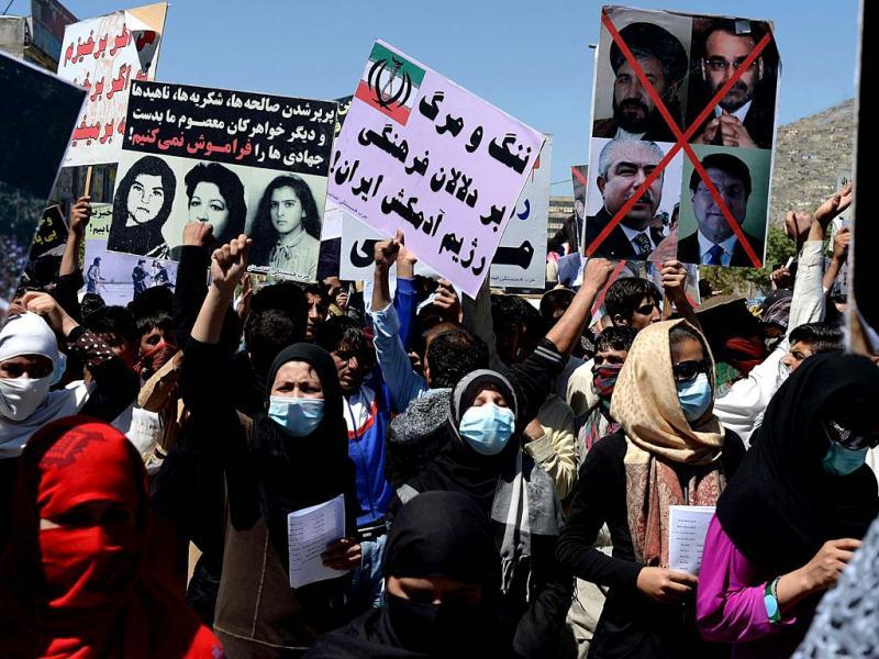 Afghan protesters shout slogans and wave placards as they take part in a demonstration staged by a pro-democracy faction in Kabul. Some hundred supporters of a pro-democracy faction took to the streets to