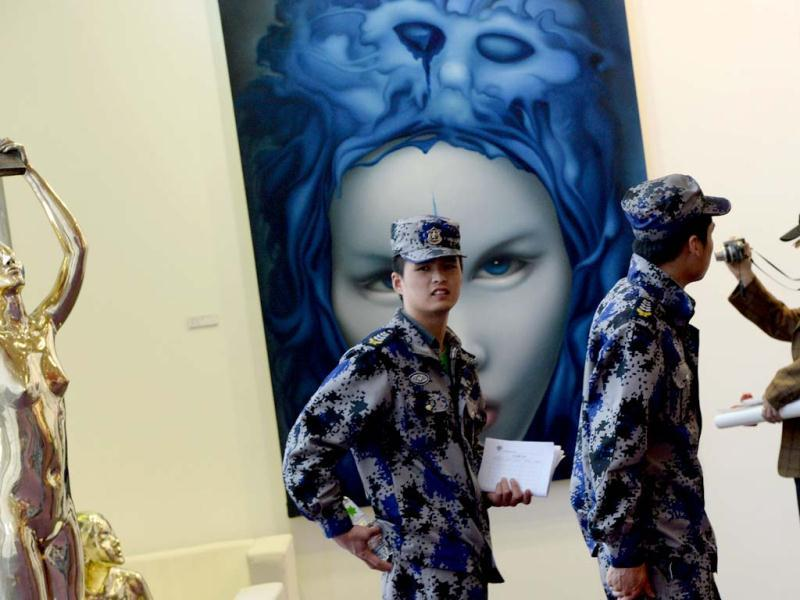 Chinese security guards walk past a painting on display at the three-day Art Beijing Contemporary Art Fair in Beijing. AFP PHOTO