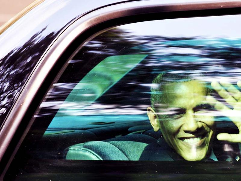 US President Barack Obama waves through the window of his car in Mexico City. (AFP)