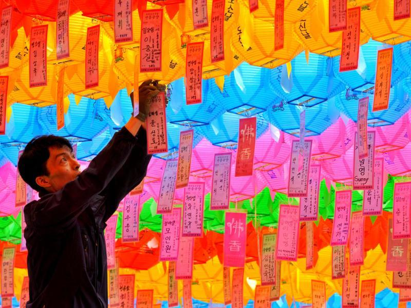 A South Korean worker attaches a name card with a wish by Buddhist followers to a lotus lantern at Chogye Temple ahead of Buddha's birthday in central Seoul. AFP