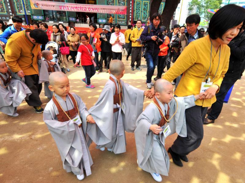 Young South Korean Buddhists with freshly shaved heads walk with their families after attending a ceremony called