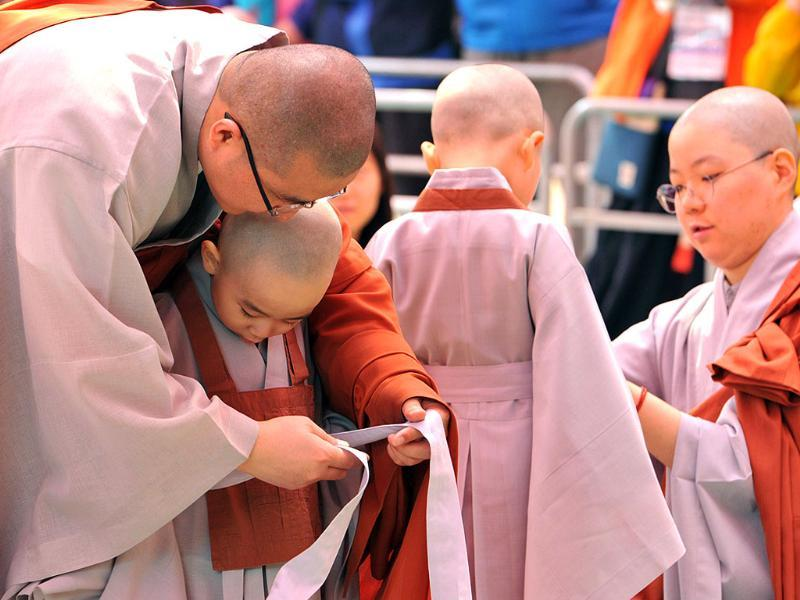 Young South Korean Buddhists are helped with their robes as they attend a ceremony called