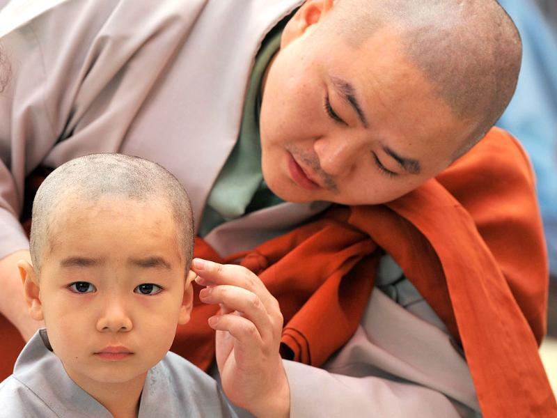 Young South Korean Buddhists with freshly shaved heads line up as they take part in a ceremony called