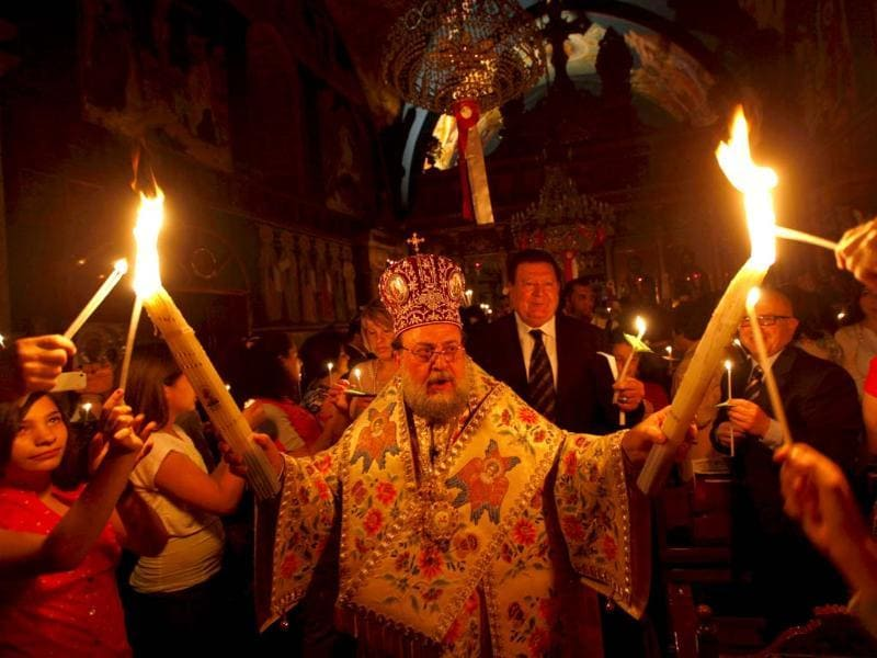 A priest holds candles during the ceremony of the Holy Fire at a Greek Orthodox church in Gaza City. Eastern Orthodox churches celebrate Easter, the resurrection of Jesus. AP