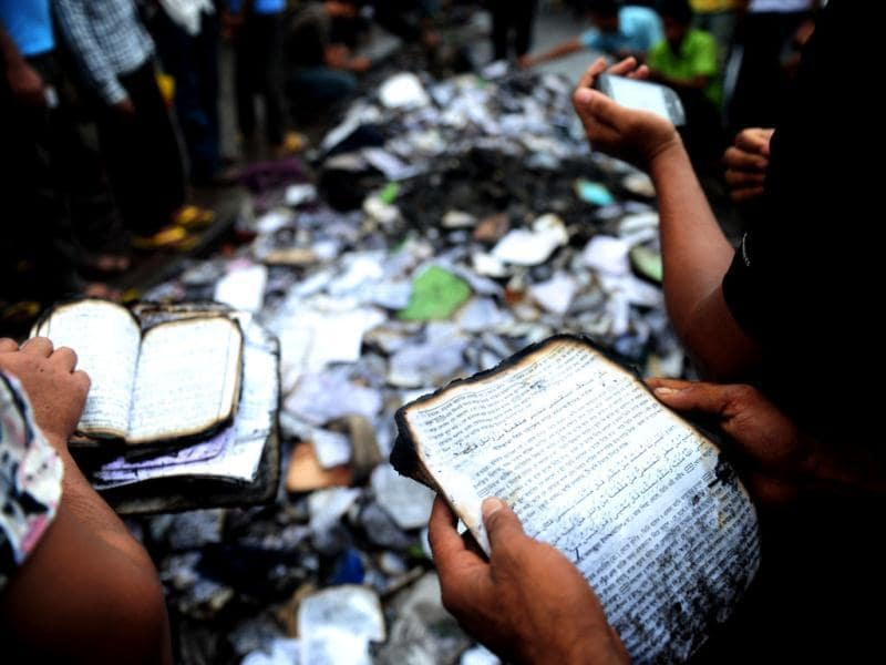 Bangladeshi people look at burnt religious literature including the Holy Quran at shops near the national mosque Baitul Mukarram following a clash between police and Islamists, in Dhaka. (AFP Photo)