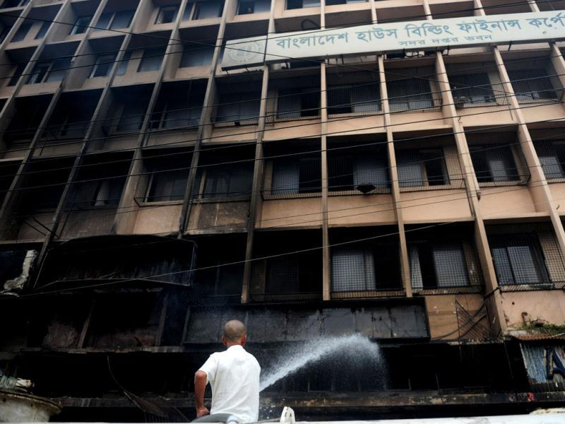 A Bangladeshi man extinguishes a blaze at a building near the premises of the national mosque Baitul Mukarram following a clash between police and Islamists, in Dhaka. (AFP Photo)