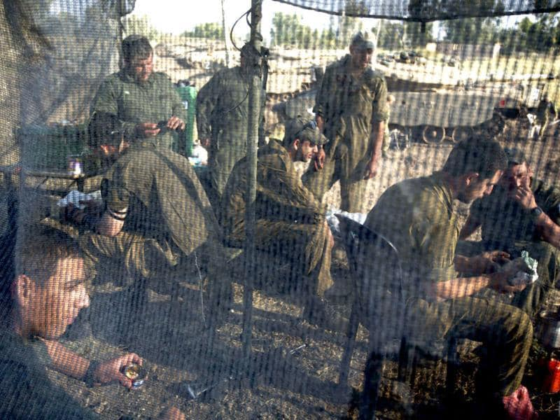 Israeli soldiers eat inside a net tent pitched close to Merkava tanks deployed in the Israeli annexed Golan Heights near the border with Syria. (AFP)
