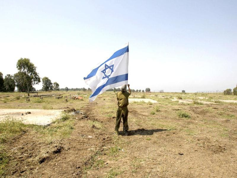An Israeli soldier places a flag close to the ceasefire line between Israel and Syria on the Israeli occupied Golan Heights. (Reuters)