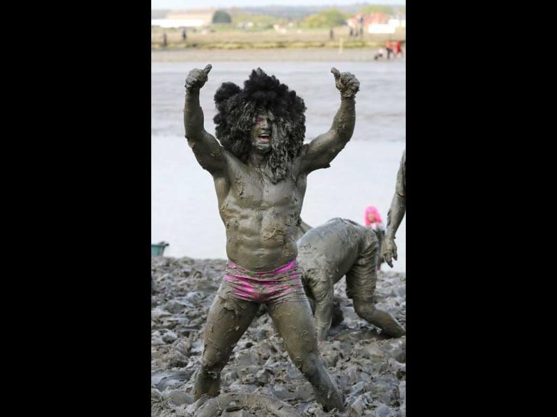 Charity fund raiser Joel Hicks celebrates as he scrambles up the river bank to the finish line of the annual Maldon Mud race in Maldon. (AP)