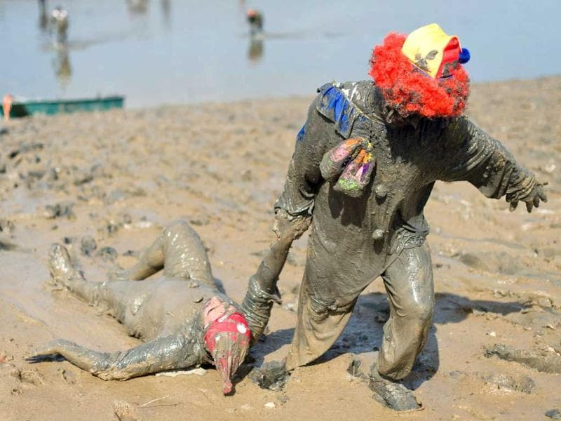 A clown helps a fallen comrade to the finish line at the end of the annual Maldon Mud Race in Maldon. (AFP)