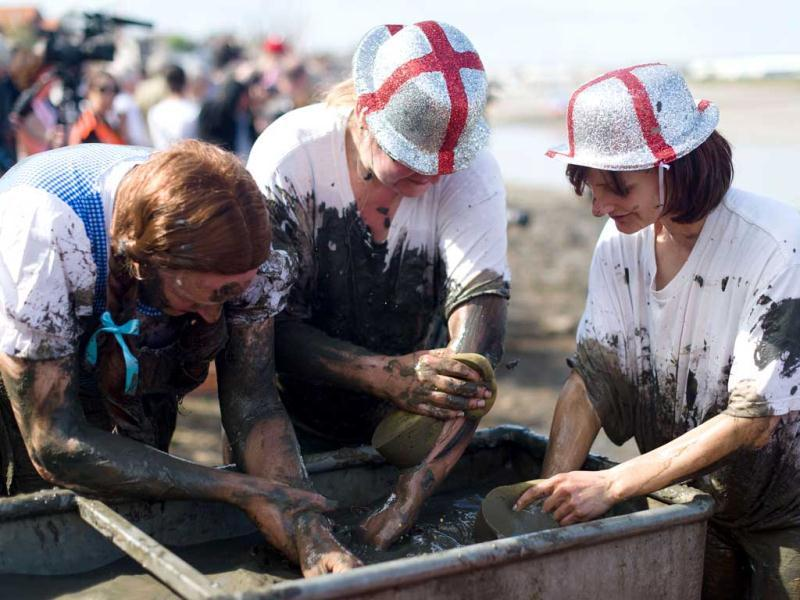 Participants wash some of the mud away at the finish line at the end of the annual Maldon Mud Race in Maldon. (AFP)
