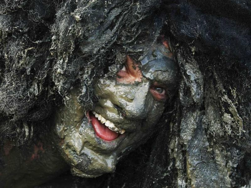 A competitor smiles at the finish of the Maldon Mud Race at the Blackwater River during low tide in Maldon. (Reuters)