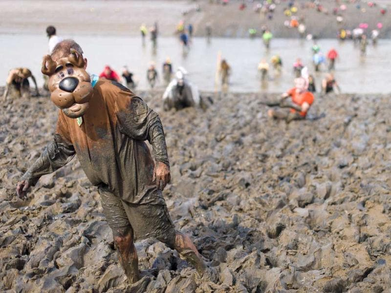 A participant reaches the finish line of the annual Maldon Mud Race in Maldon, Essex. (AFP)