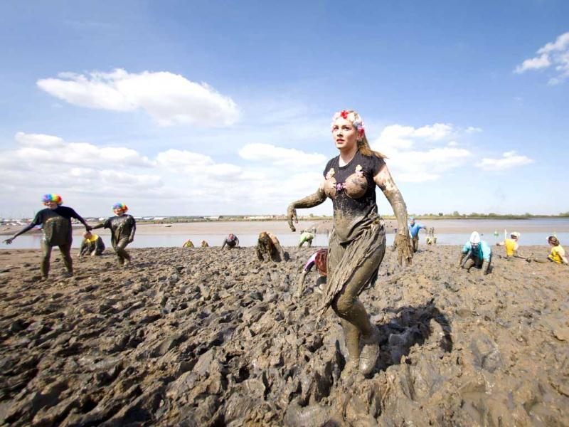 A participant reaches the finish line of the annual Maldon Mud Race in Maldon. (AFP)