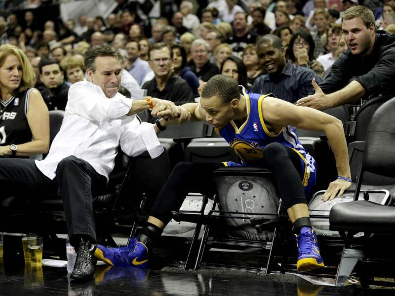 After making a three-point basket against the San Antonio Spurs, Golden State Warriors point guard Stephen Curry his helped when he fell into the seats during the second half of Game 1 of a Western Conference semifinal NBA basketball playoff series in San Antonio. AP Photo