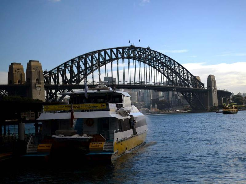 A man washes his boat in front of the iconic Sydney Harbour Bridge. AFP