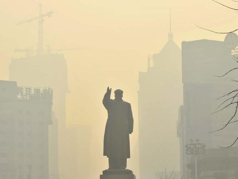 A statue of China's late chairman Mao Zedong is seen in front of buildings during a hazy day in Shenyang, Liaoning province. Reuters