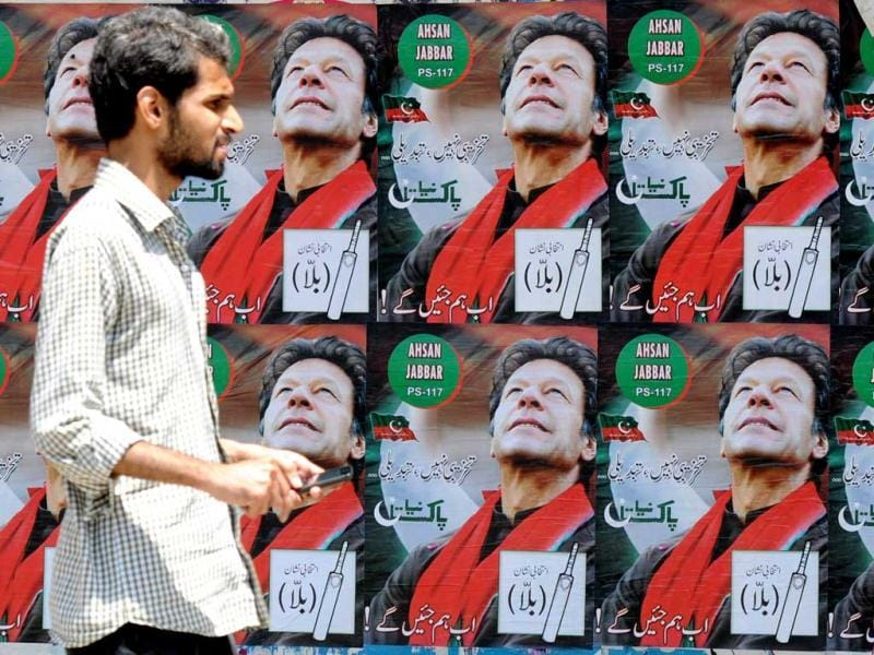 A Pakistani pedestrian walks past electoral posters of Pakistani politician and former cricketer Imran Khan, in Karachi. Pakistani politician Imran Khan has been advised to rest for a week after sustaining skull and back injuries in a fall at an election campaign rally, a hospital official said. The former cricket star was admitted to the private Shaukat Khanum hospital that he founded in Lahore on May 7 after falling off a lift taking him to the stage at a rally ahead of Pakistan's general election on Saturday. (AFP)