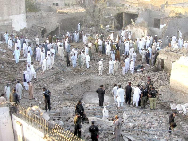 People gather at the site of a bombing in Bannu, Pakistan. On Wednesday, a suicide bomber detonated a car packed with explosives outside a police station in the city of Bannu in Khyber Pakhtunkhwa, killing a person and wounding others, police officer Rafiq Khan said. (AP)