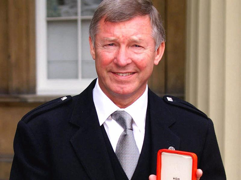 A picture taken on July 20, 1999, shows Manchester United soccer manager Sir Alex Ferguson holds his knighthood insignia that was presented to him by Britain's Queen Elizabeth during an Investiture ceremony at Buckingham Palace, London. (AP)