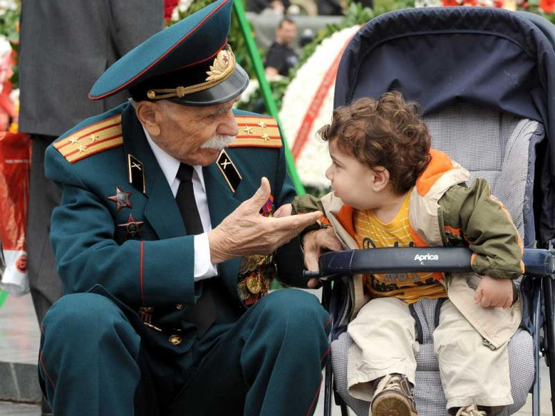 A World War II veteran speaks with a little child during Victory Day celebration in the Armenian capital Yerevan. AFP PHOTO