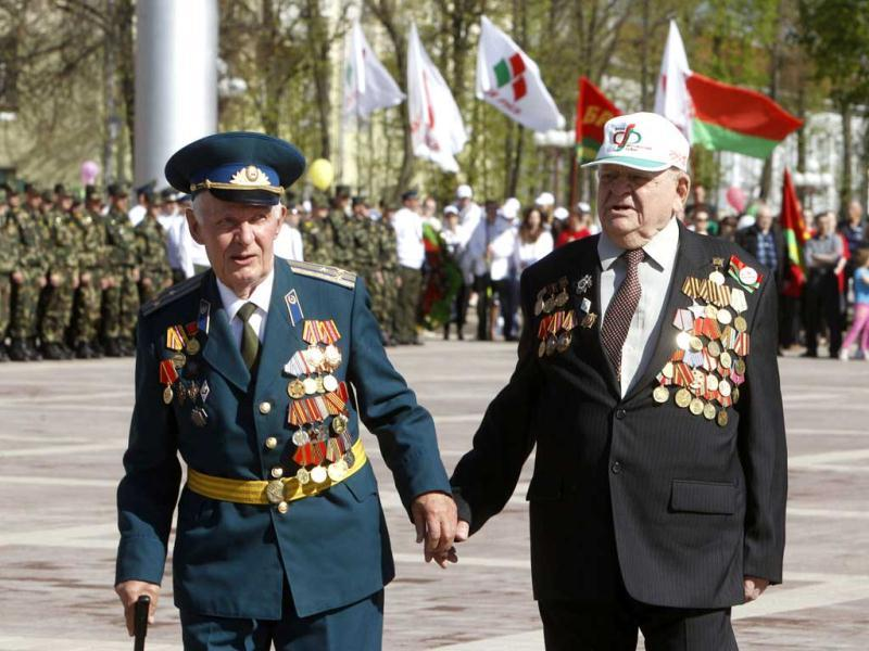 World War Two veteran Pavel Ryzhkovsky, 91, (R) walks with Soviet army veteran Vitaly Epimakhov during Victory Day celebrations in the town of Molodechno, some 60 km (37 miles) northwest of Minsk. REUTERS