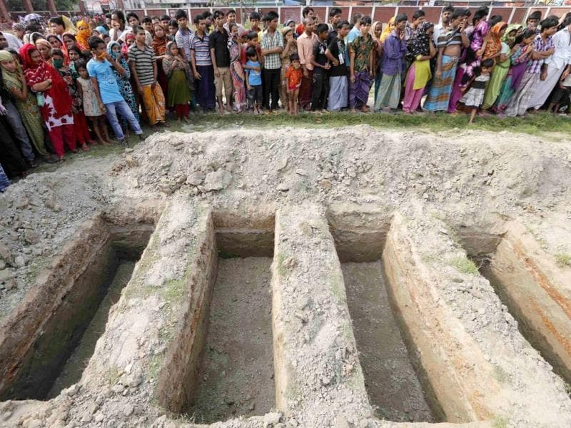 People gather in front of mass graves during the burial of unidentified garment workers, who died in the collapse of the Rana Plaza building in Savar, in Dhaka. Reuters photo